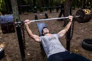 man in grey shirt and black bottom lifting barbell